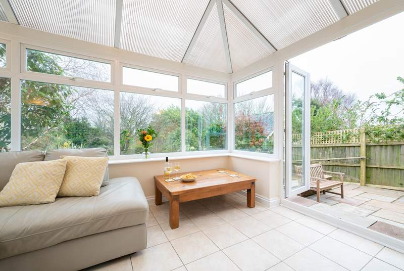 Appreciate the light and airy conservatory leading out to the garden.