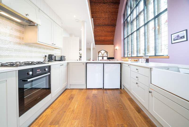 The light from the stained glass windows floods in to the bright and modern kitchen.