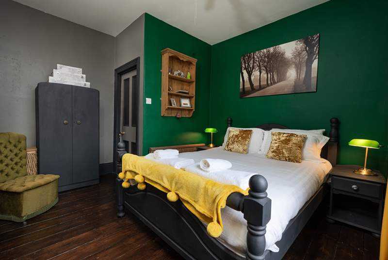 The dark walls and furniture complement the original wood flooring in this handsome bedroom.