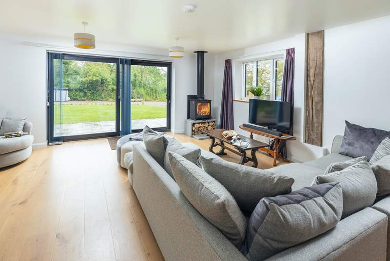 The fabulous living-room has a super-comfy corner sofa and patio doors to the garden.