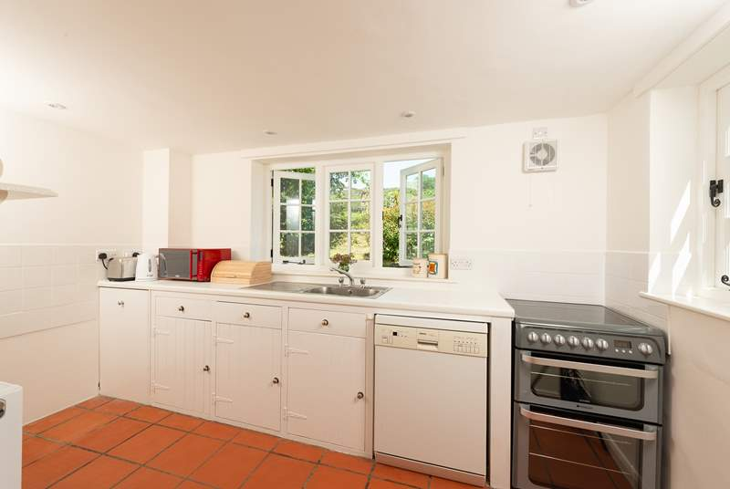 The farmhouse-style kitchen is split into two areas, with plenty of storage and worktop space in its totality.