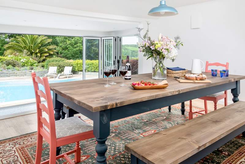 The dining-room is accessed through the kitchen and up three steps which gives you an lovely elevated view over the pool and through the picture window.