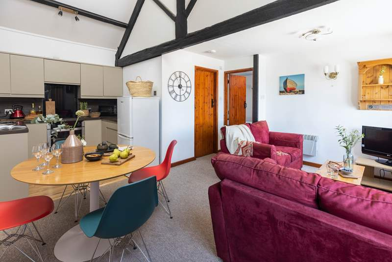 The open plan living area with double height ceilings and exposed beams.
