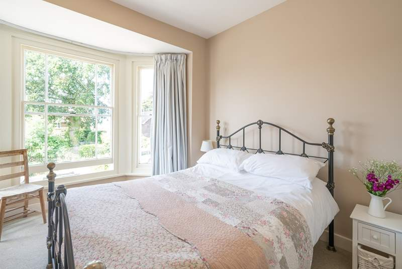 The pretty main bedroom is furnished with an ornate, comfy double bed.
