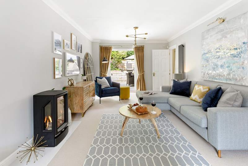The fabulous sitting-room with beautiful, contemporary furnishings and access through the patio doors to the outside space.