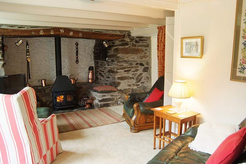 A welcoming wood-burner nestles in the huge inglenook fireplace.