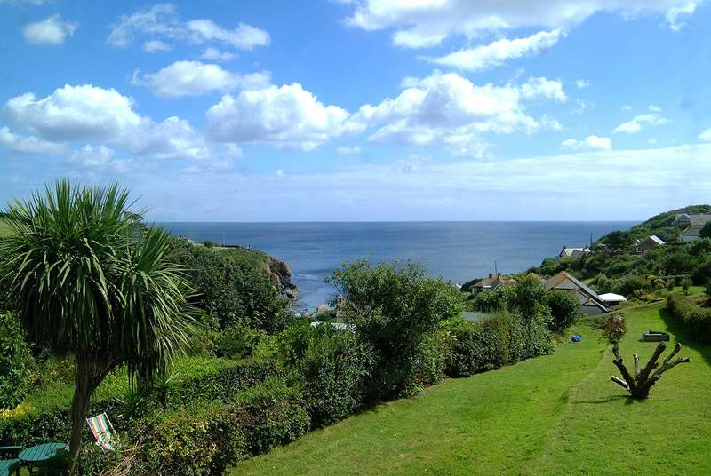 The stunning view from two of the bedrooms across the cottage garden to the cove and beyond.