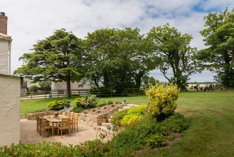 The large garden wraps around the rear and front of the cottage.