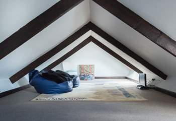 The galleried den up under the eaves is accessed via a wooden ladder from the sitting-room, the beanbags are great for children to lounge on and watch television.