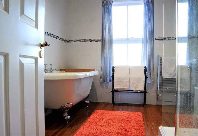 The lovely big family bathroom has a claw-foot bath and a big walk-in shower cubicle.