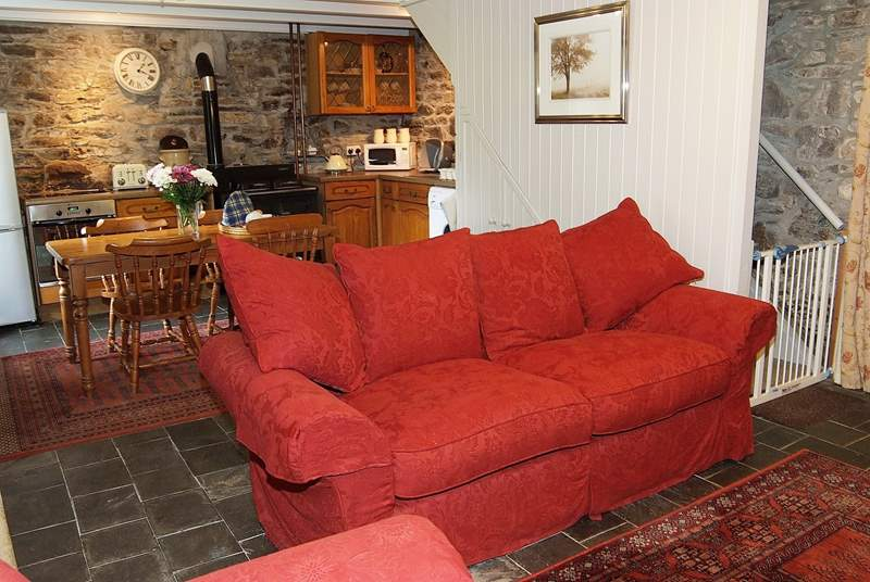 Large sofas sit in front of the wood-burner.