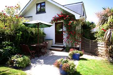There are two steps up to the front door from the sunny garden.