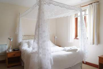 The lovely four poster bed is dressed with snowy white drapes.