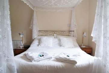 Crisp white linens and lace make the bedroom restful.