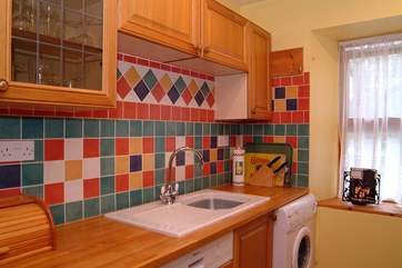 Colourful tiles brighten the kitchen.