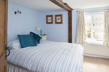 This tranquil double bedroom looks out over the garden at the back of the cottage.