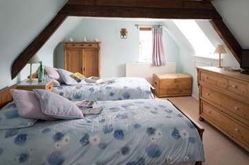 The twin bedroom at the top of the cottage on the second floor, children can look out of the window at the steam train that runs past the side of the garden.