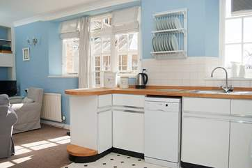 The kitchen-area has wooden work surfaces, a small dishwasher and plenty of cupboard space.