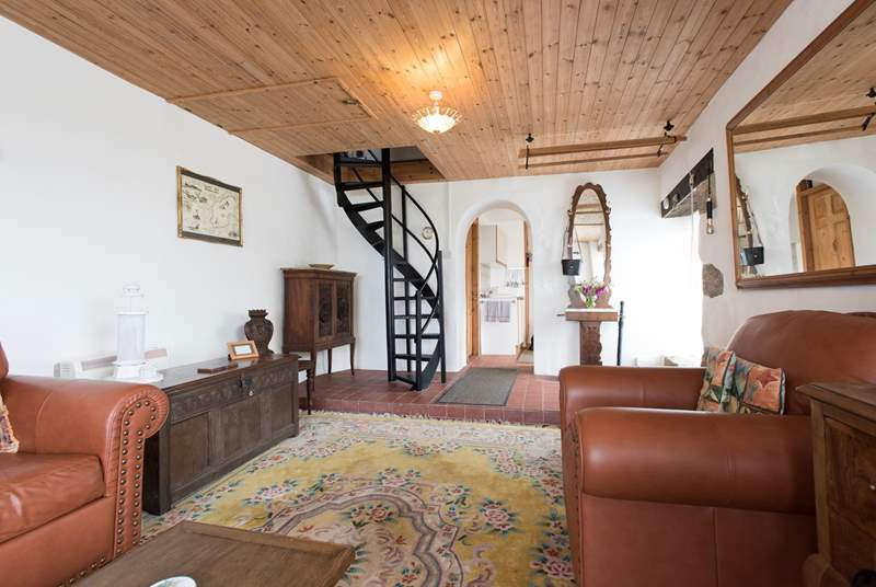 The sitting-room has a steep spiral staircase to the first floor bedroom.