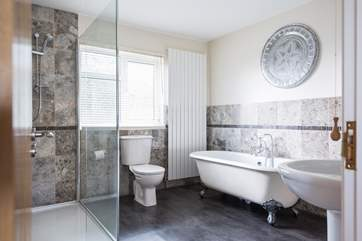 The family bathroom includes a large walk-in shower as well as a free-standing roll-top bath.