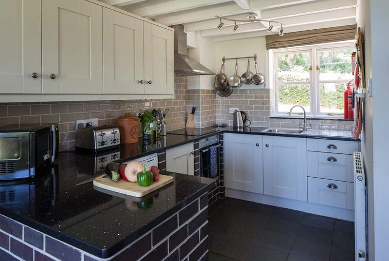 The kitchen is in one corner of the open plan living space and is very well-equipped. The window looks out onto the enclosed rear courtyard.