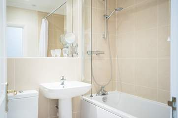 The well-appointed family bathroom has a bath with fitted shower above.