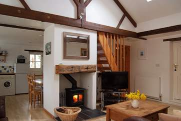 The L-shaped open plan living-room includes a welcoming wood-burner at the centre.