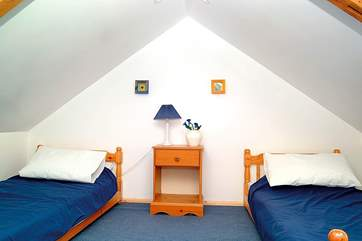 Bedroom 3 has sloping ceilings and is furnished with low single beds.