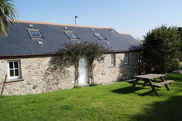 The exterior of the cottage, which has an enclosed lawned garden alongside it.