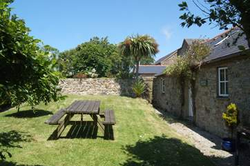The cottage garden is bordered by mature hedges and shrubs and a lovely stone wall.