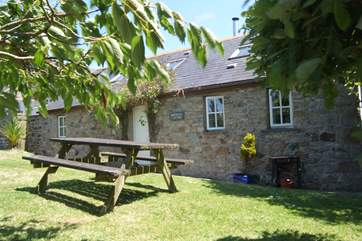 The lawn alongside the cottage is bordered by mature hedges and shrubs.