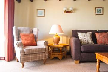 Table lamps and cushions add to the comfort in the sitting-room.