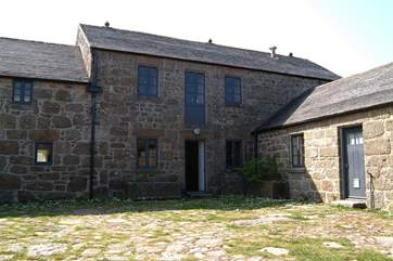 The entrance to the cottage and front courtyard, showing the semi-detached property to the right.