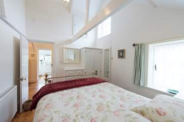 The bedroom shares the high ceiling and light, airy feel of the rest of the cottage.