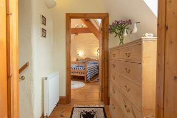 A little landing separates the two bedrooms. More storage space is offered in the large chest of drawers.
