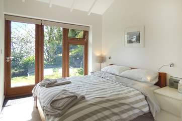 The comfortable double bedroom has a king-size bed and a glass door opening onto the garden decking.