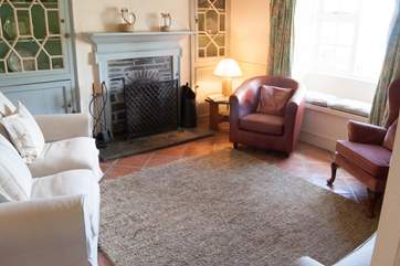 The sitting-room has comfy chairs and sofas around a cosy open fire and fabulous views.