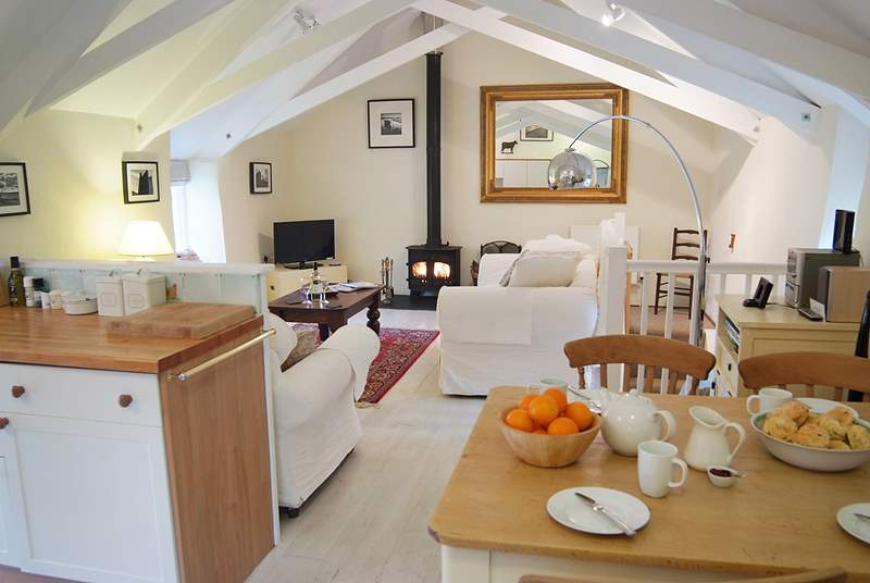 The living-room has an open beamed ceiling, lime-washed wood floors and a cosy wood-burner.