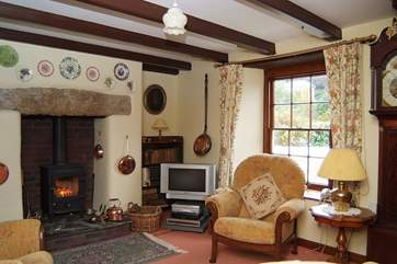 The sitting-room is traditionally furnished and includes a welcoming wood-burner.