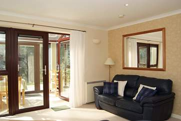 The conservatory floods light into the sitting-room.