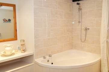 The large family bathroom has a corner bath with electric shower.