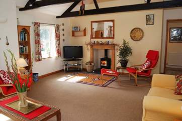 The comfortable sitting-room has a vaulted ceiling with the original wooden beams.