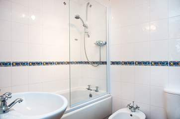 The bathroom is light and airy and has a fitted shower over the bath