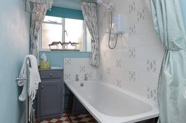 The bathroom is downstairs and has a pretty colour scheme and is a warm and cosy room.