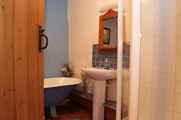 The pretty bathroom has a roll-top bath as well as a separate shower.
