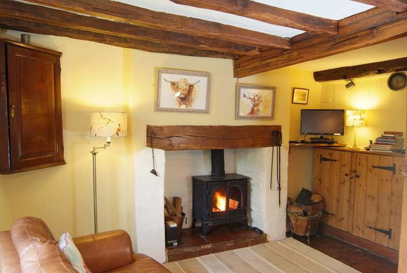 This beamed room is the  heart of the cottage. It has a wood burning stove and a comfortable sofa to relax in at the end of a day out walking
