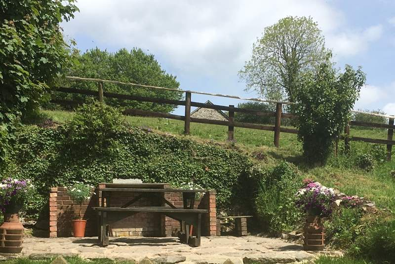 The garden has a lawned area, a paved terrace, seating and a barbecue. There are just a few stone steps up to the garden.