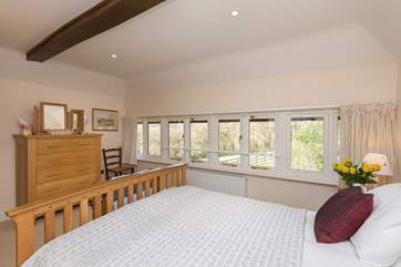 The windows stretch for the full width of the room so you can lie in bed and look at the woodland across the field.