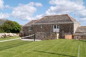 The grass tennis court in the garden.