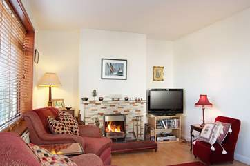 The sitting-room has a flat screen television and an open fire.